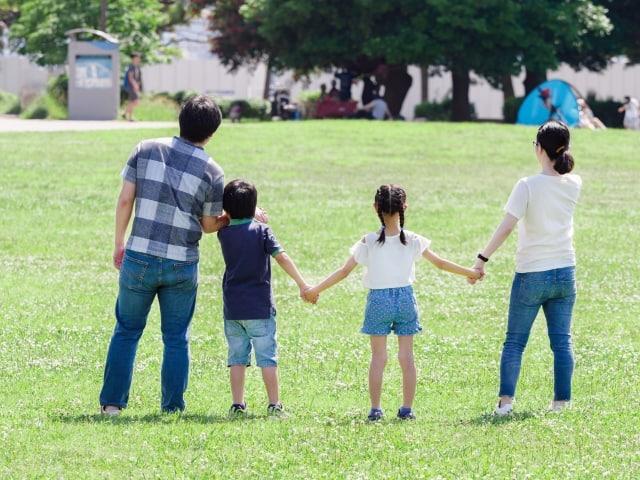 手を繋いでいる家族4人