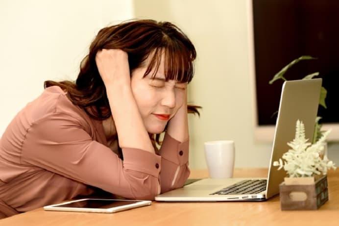 パソコンを開いて悩んでいる女性