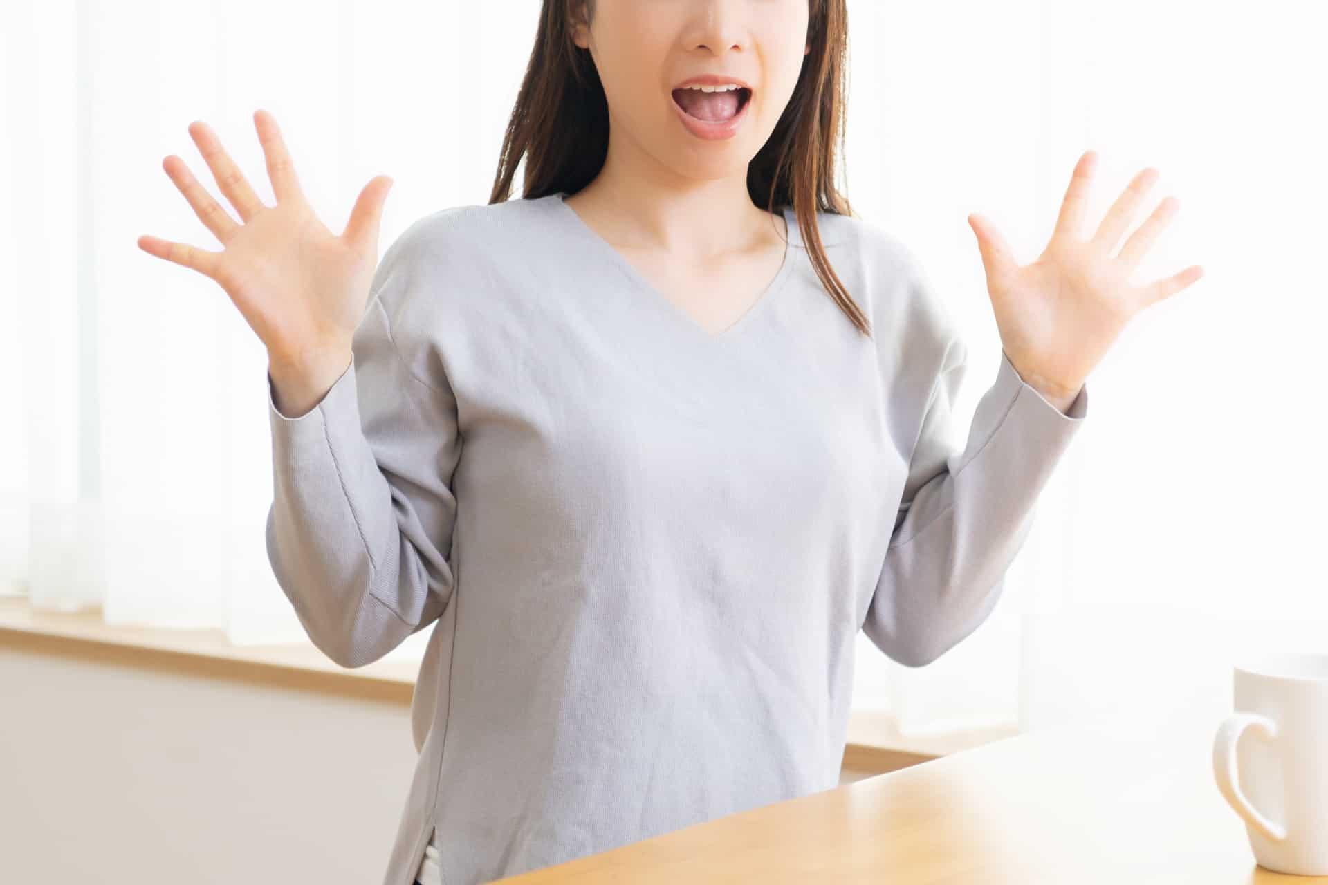 両手を広げて驚く女性
