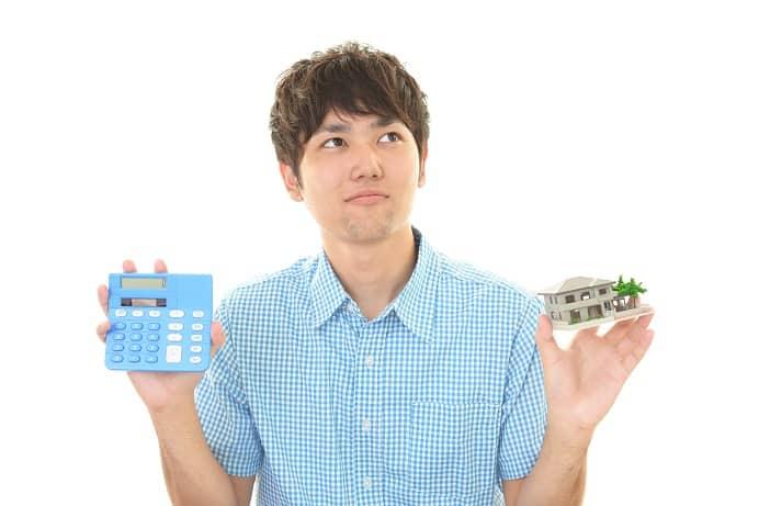 男性が電卓と家の模型を持っている