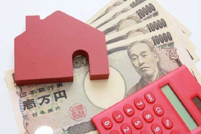 一万円札の上に電卓と家の模型