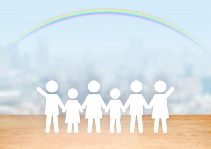 手を繋いでいる人たちの上に虹がかかっている